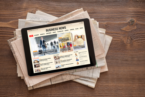 Newspapers and tablet with business news