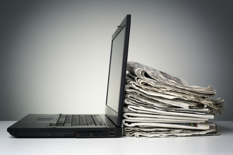 Stack of newspapers next to laptop